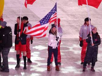 d02710-20180225-jessie-diggins-carries-flag-at-2018-winter-olympic-games-closing-ceremony